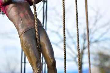 Woman in dirty sportswear climb the rope