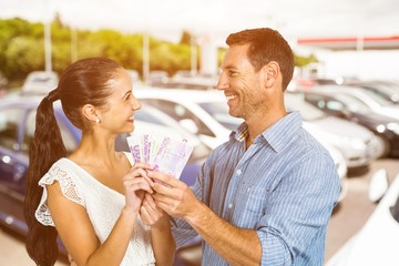 Composite image of smiling couple holding money