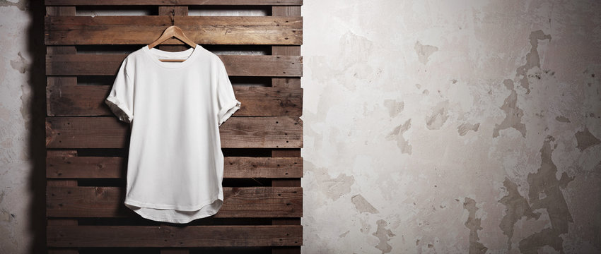 Photo white tshirt  hanging in front of concrete wall. Wide