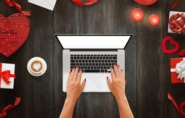 Girl work on laptop with isolated screen on a wooden background. Love decorations beside, coffee, gifts, candles, hearts