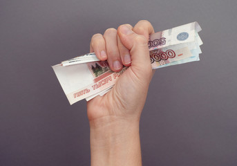 Woman hand squeezes russian money