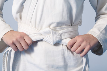 Photo sur Aluminium Combat Hands tightening white belt on a teenage dressed in kimono