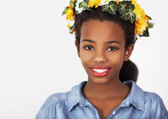 Beautiful girl with wreath of flowers in her hair Young pretty African girl with flowers in a hair, isolated on white background. Head and shoulders. Studio shoot.