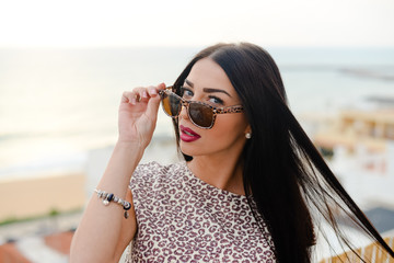Beautiful girl in sunglasses over ocean and sky background