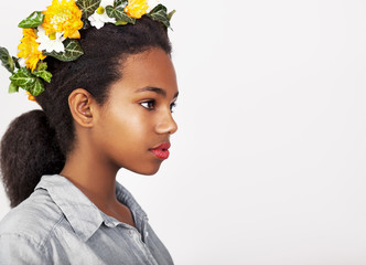 Young pretty African girl with flowers in a hair, isolated on white background. Head and shoulders. Studio shoot.