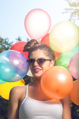 Girl posing with balloons in nature