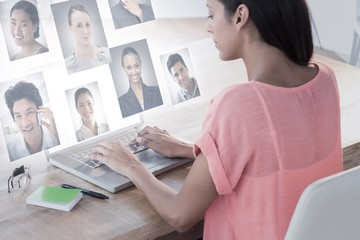Composite image of businesswoman using laptop at desk