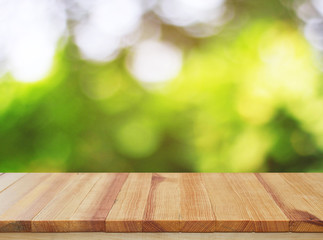 Wood table top on green bokeh abstract background - can be used for montage or display your products