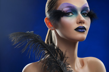 Queen of blue. Studio portrait of an attractive young woman wearing professional creative makeup in blue tones with feather attachments