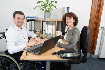 Man in wheelchair sat at desk with his female colleague
