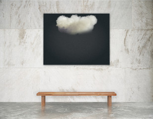 Black picture with white cloud on the wall above wooden bench on