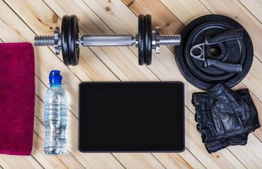 Sport Equipment. Dumbbells, Free Weights, Barbell, Hand Grip, Sport Gloves, Towel, Bottle Of Water And Digital Tablet To Workout Plan On Wooden Boards. Sport Fitness Background