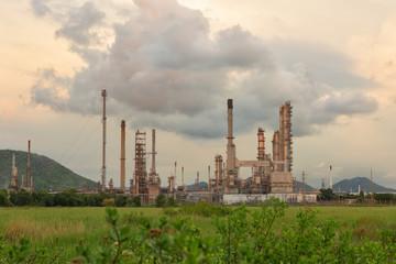 Twilight scene of oil refinery plant on dark cloud background.