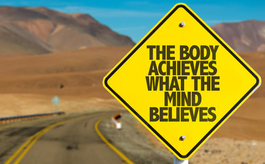 The Body Achieves What The Mind Believes sign on desert road