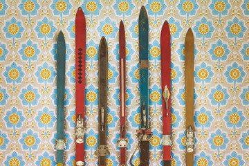 Vintage colorful used skis in front of retro wallpaper