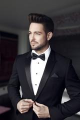 Sexy man celebrity in tuxedo indoor