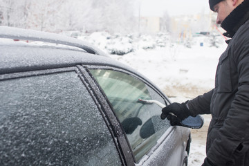 man cleans snow from car window