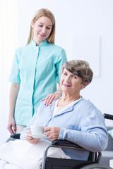 Nurse assisting disabled senior woman