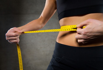 close up of woman measuring waist by tape in gym