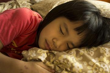 little girl sleeping on bed