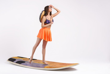 Vacation. Delightful model on white background looks into the distance, standing on a surfboard.