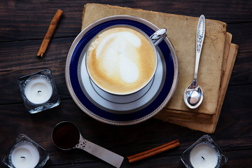 Coffee composition with old book, white tea candles, silver spoon, ground coffee and cinnamon on dark wooden background.