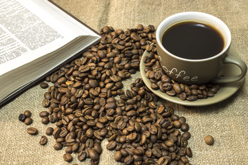 A cup of coffee with scattered coffee beans and open book are  stands on a piece of burlap