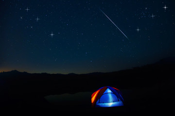 Camping tent under stars at night