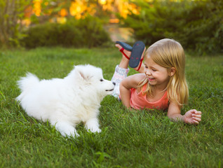 Little smiling girl playing with Samoyed puppy in the summer gar