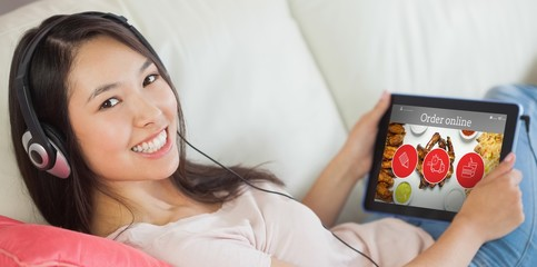 Composite image of girl using her tablet pc on the sofa