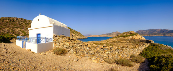 Panoramic view of white chapel at beautiful ocean coastline, Gre