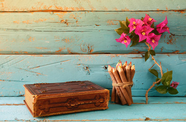 vintage notebook and stack of wooden colorful pencils on wooden texture table next to purple bougainvillea flower. vintage filtered and toned image