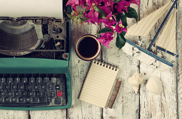 image of vintage typewriter, blank notebook, cup of coffee and old sailboat on wooden table