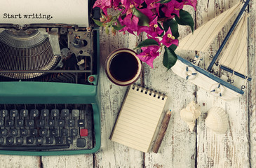 "image of vintage typewriter with phrase ""Start writing"", blank notebook, cup of coffee and old sailboat on wooden table"
