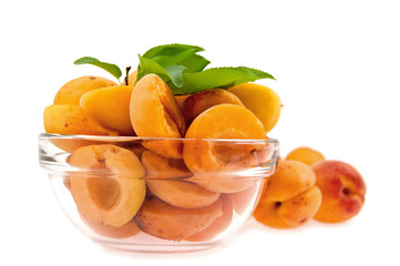 halves apricot in a dish on a background whole apricot