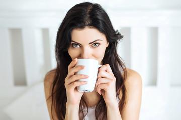 Frau trinkt Kaffee im Bett