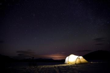 beleuchtetes Zelt im Winter in Schweden mit leichten Nordlichtern im Hintergrund