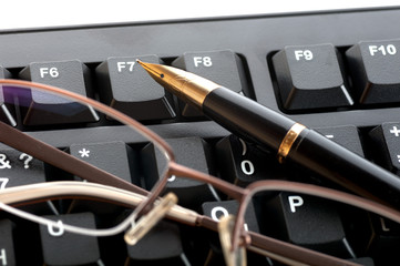 pen with a golden feather and glasses is on the black keyboard