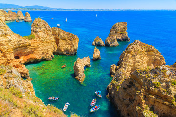 Fishing boats on turquoise sea water at Ponta da Piedade, Algarve region, Portugal Fototapete