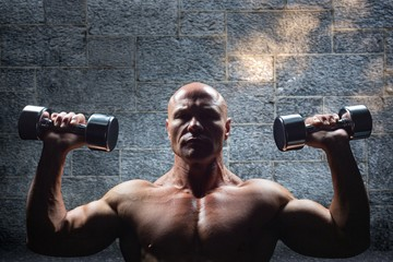 Composite image of portrait of man exercising with dumbbells