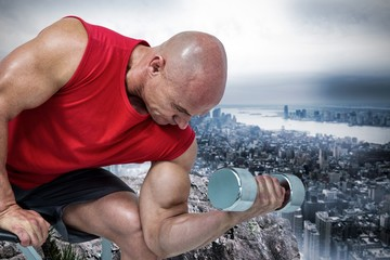 Composite image of bald man exercising with dumbbells