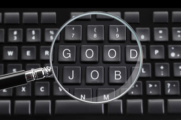 GOOD JOB written on keyboard with magnifying glass