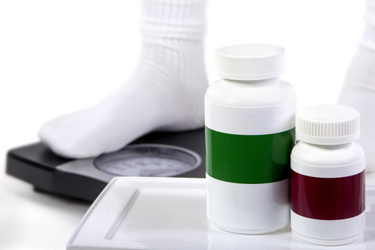 Weight loss or gain pill bottle with copyspace and feet on a scale