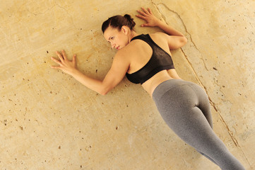 Woman with good health with a black top and gray yoga pants against a wall
