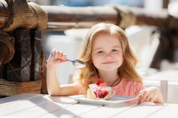 Little girl eating cake with strawberries in the summer cafe