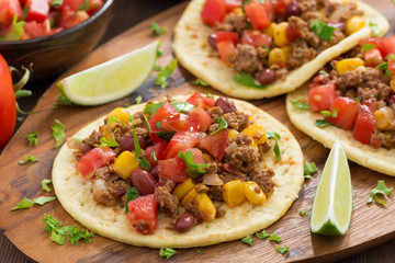 tortillas with chili con carne and tomato salsa on wooden board
