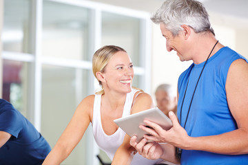 Trainer mit Tablet Computer redet mit Frau