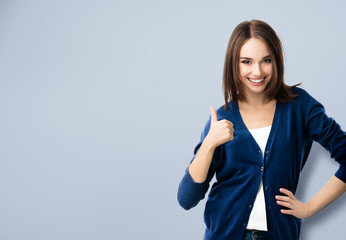 young woman showing thumbs up gesture, with copyspace
