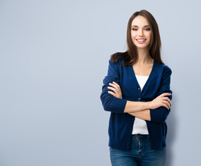 smiling young woman with crossed arms, with copyspace