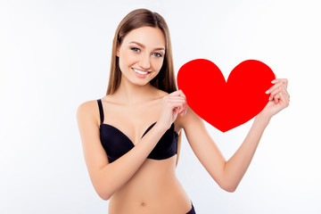 Young sexy happy woman in black bra holding red paper heart